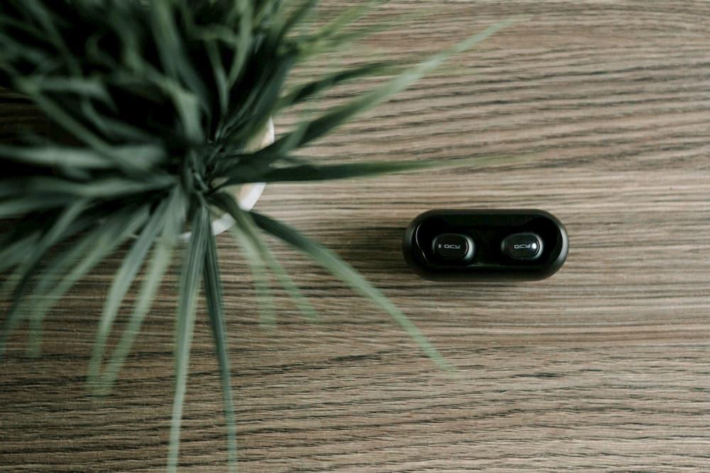 Imagen de unos auriculares Bluetooth al lado de una planta, encima de una mesa de madera.
