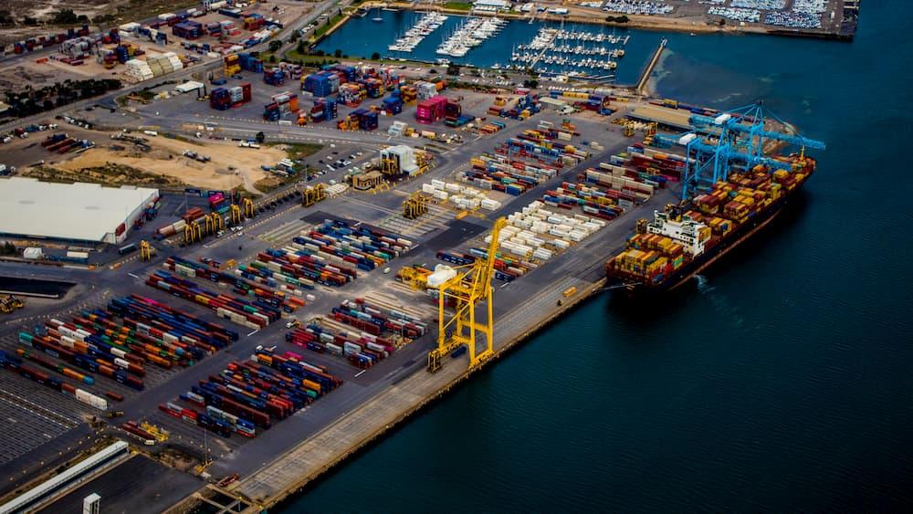 Imagen de un puerto recibiendo barcos con mercancía para entregar en containers.