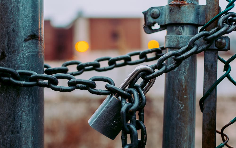 Imagen de un candado con cadena cerrando una pierta