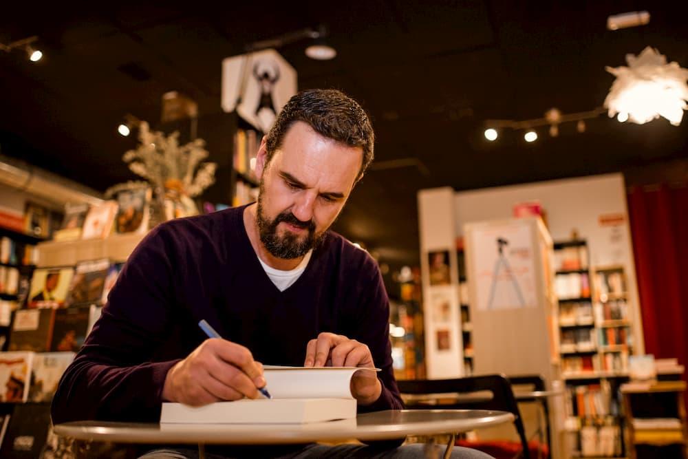 Imagen de Carlos Losada firmando un autográfo en una copia de su libro Hijos del impacto.