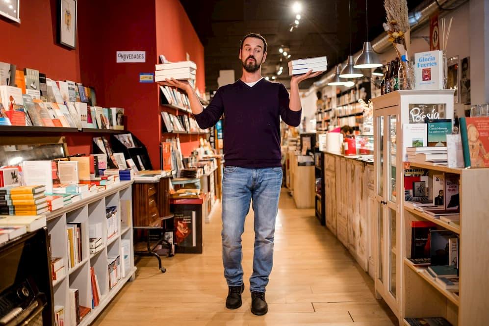 Imagen de Carlos Losada sujetando dos libros, uno en cada mano