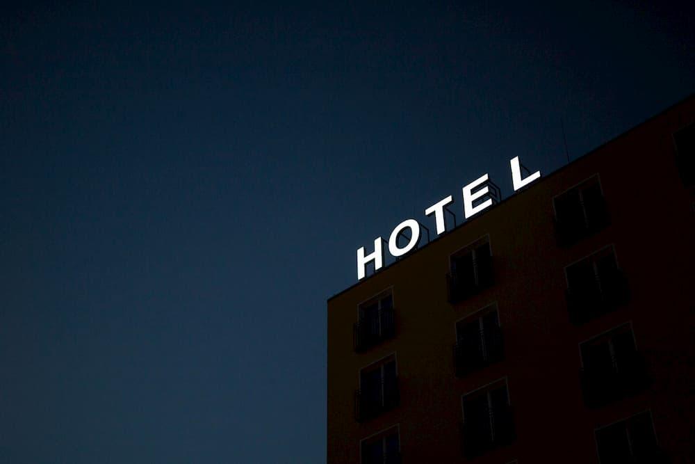 Imagen de un hotel con su cartel luminoso encendido por la noche.