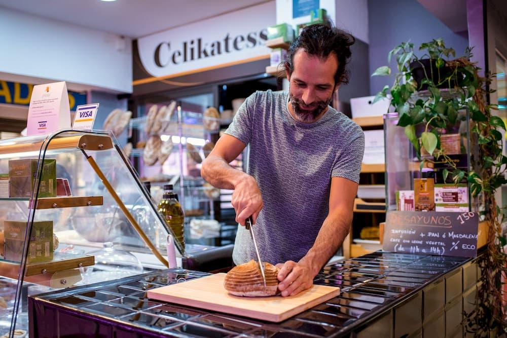 Imagen de Sergio Del Rey cortando pan en su obrador de Celikatessen
