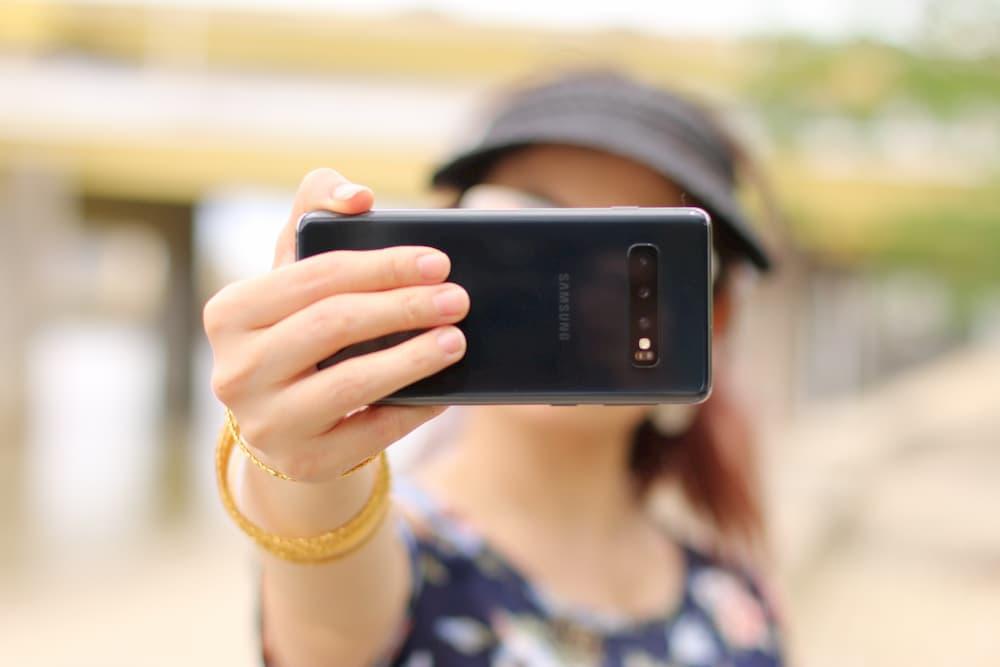 Imagen de una chica grabando un vídeo en modo selfie desde su móvil