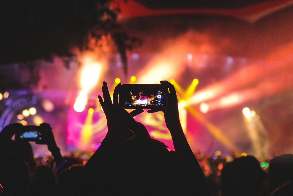 Imagen de una chica sujetando un móvil grabando un concierto, para subirlo luego a una red social como Vine