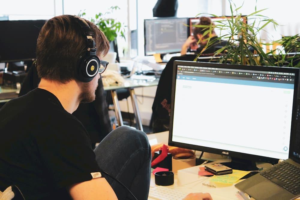 Imagen de un chjco trabajando con el ordenador de empresa, usando unos auriculares para concentrarse.