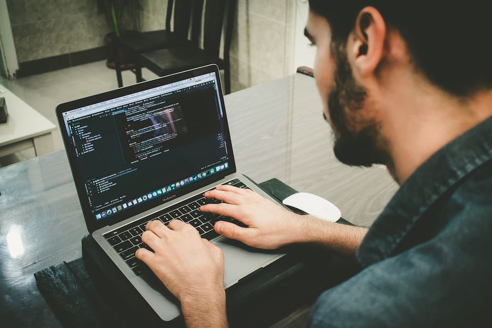 Imagen de un chico escribiendo código con un portátil
