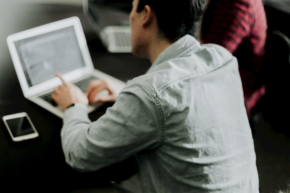 Imagen de un chico joven trabajando con su portátil gestionando su negocio.