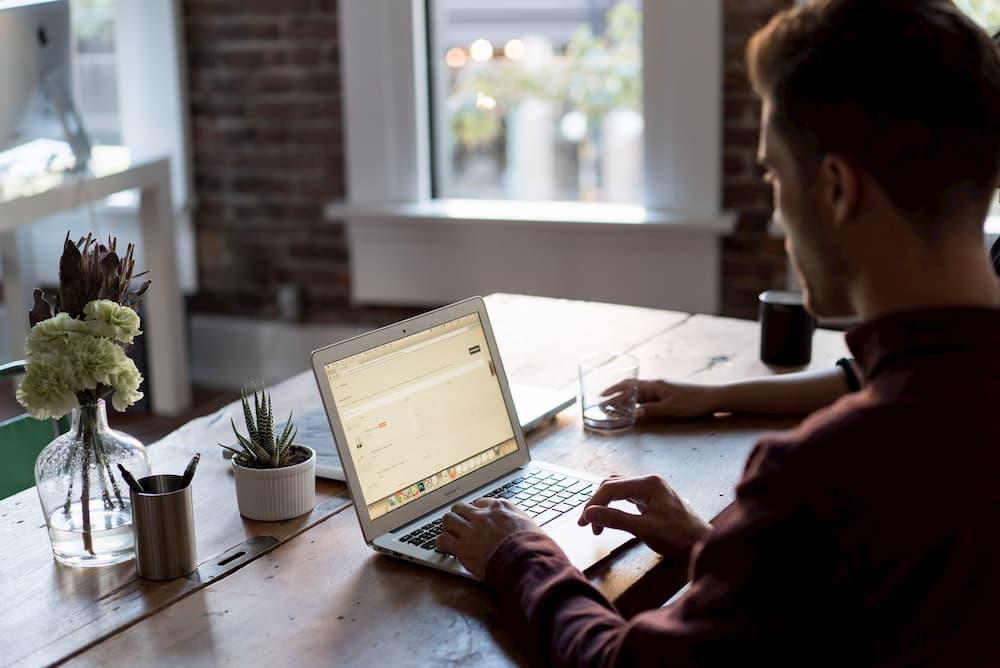 Imagen de un chuco trabajando con su portátil en su despacho, en una mesa de madera.
