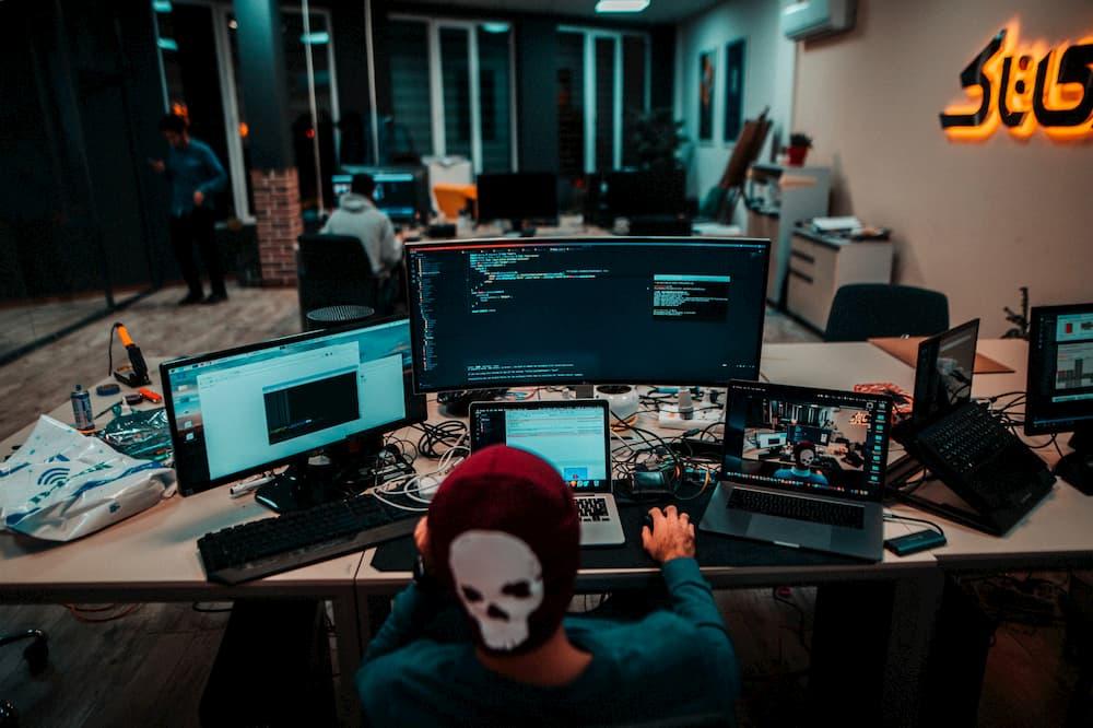 Imagen de un chico trabajando con varias pantallas en su puesto de trabajo