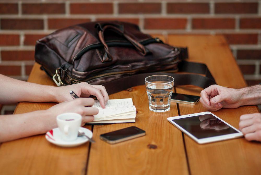 Imagen de dos personas charlando con un café en una mesa de madera