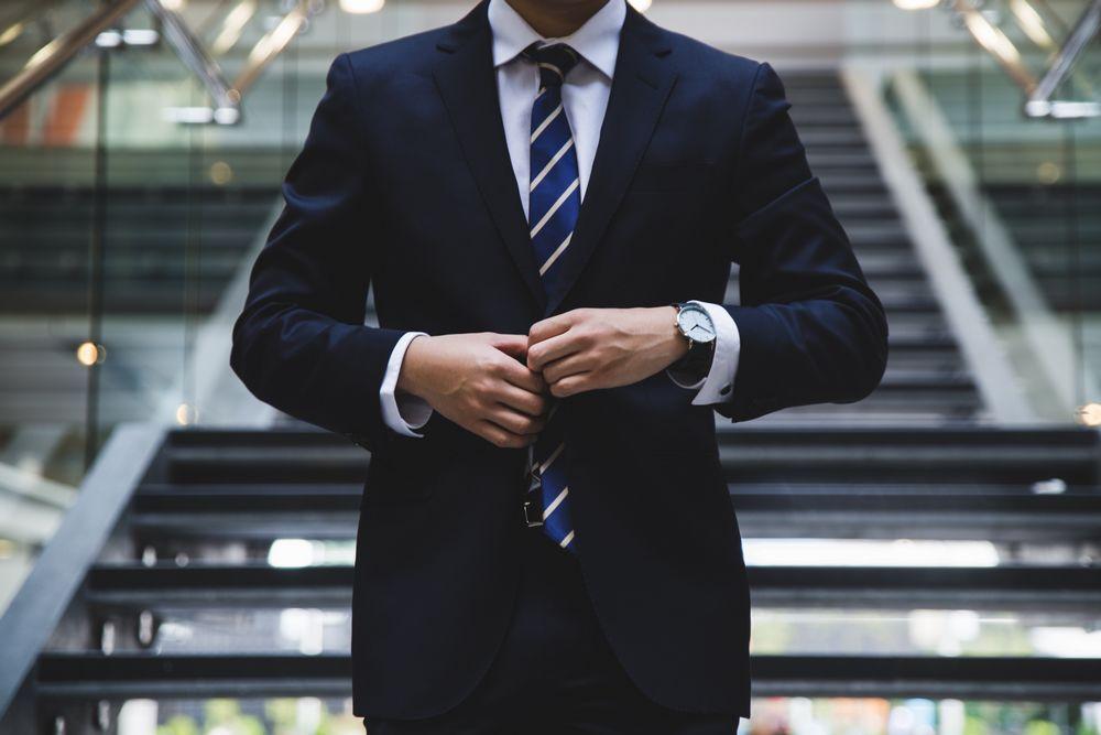Imagen de un hombre de negocios trajeado abrochándose la chaqueta