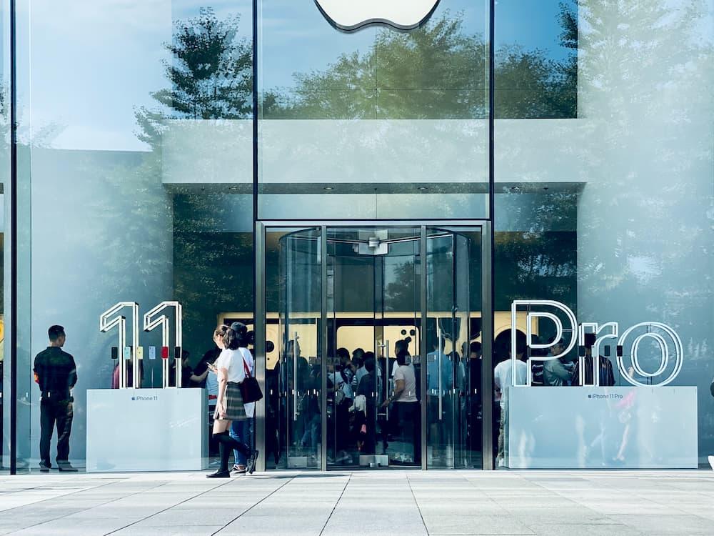 Imagen del exterior de una tienda Apple donde se anuncia el lanzamiento del iPhone 11 Pro con muchos clientes esperando.