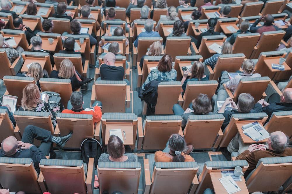 Imagen de gente reunida en una sala de conferencias, asistiendo a un ejemplo de comunicación corporativa de una empresa.