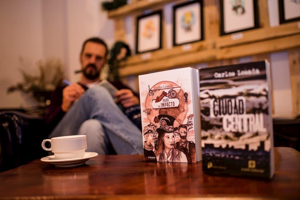 Imagen de los libros Hijos del impacto y Ciudad Central, de Carlos Losada, con su autor al fondo