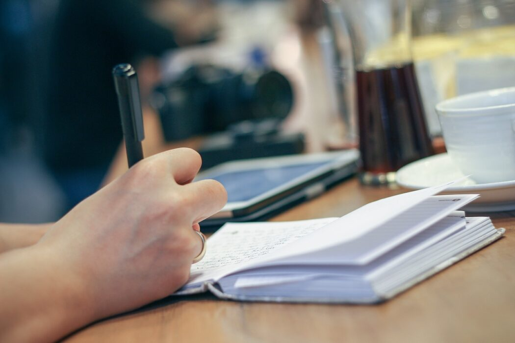Imagen de un chico tomando notas en una libreta al lado de un ordenador