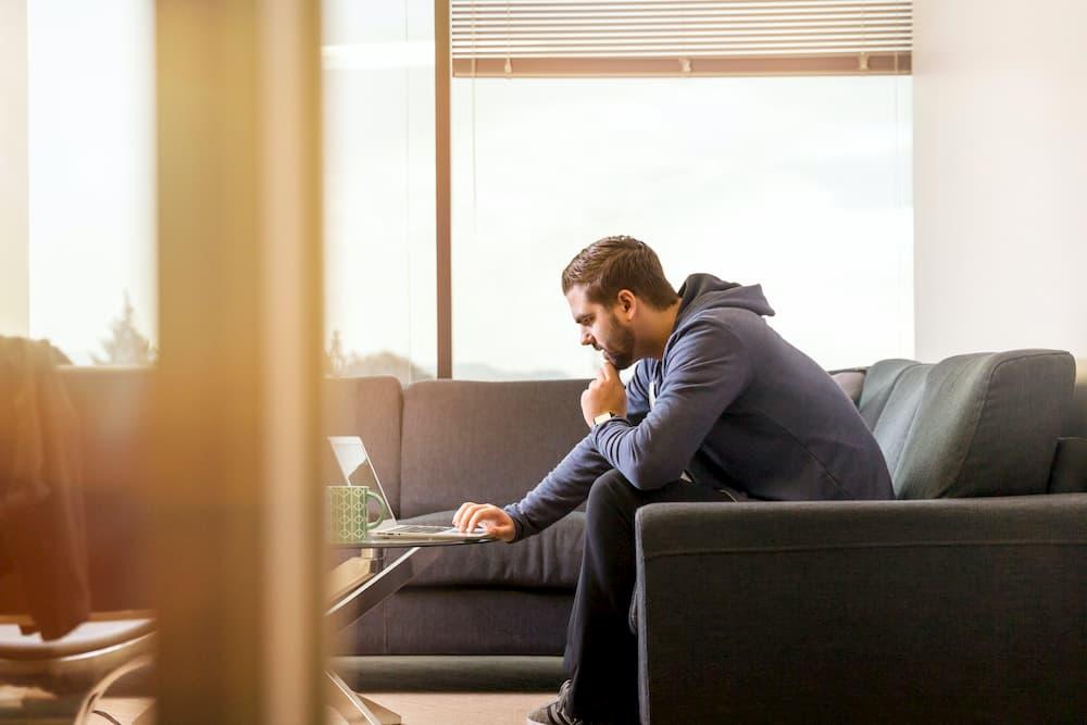 Imagen de un hombre consultando las preguntas frecuentes de una página web desde su portátil.