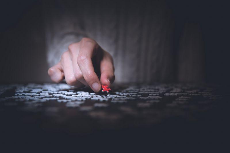 Imagen de un hombre sujetando una pieza de puzzle de color rojo
