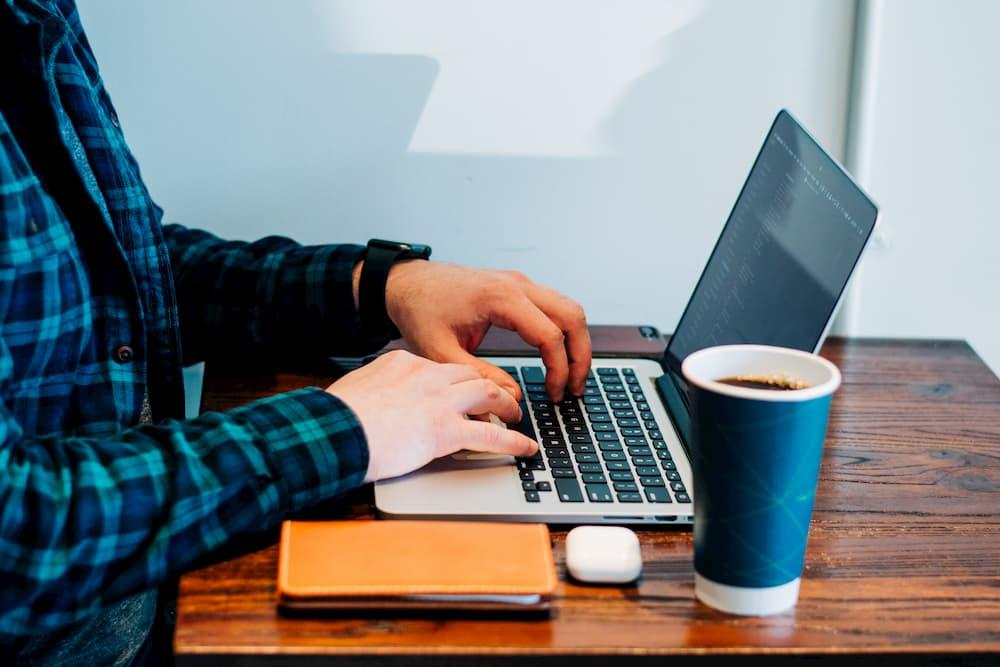 Imagen de un hombre viendo en un portátil cómo conseguir suscriptores en YouTube