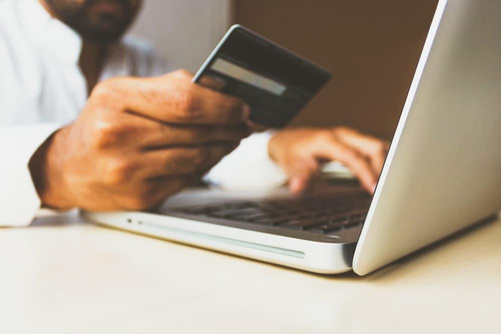 Imagen de un hombre usando una tarjeta de crédito, quizá sin saber qué es un scam y esté enfrentándose a una página web fraudulenta