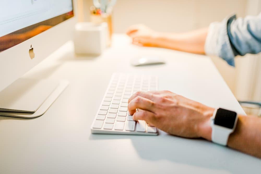 Imagen de un hombre escribiendo usando el teclado de in iMac.