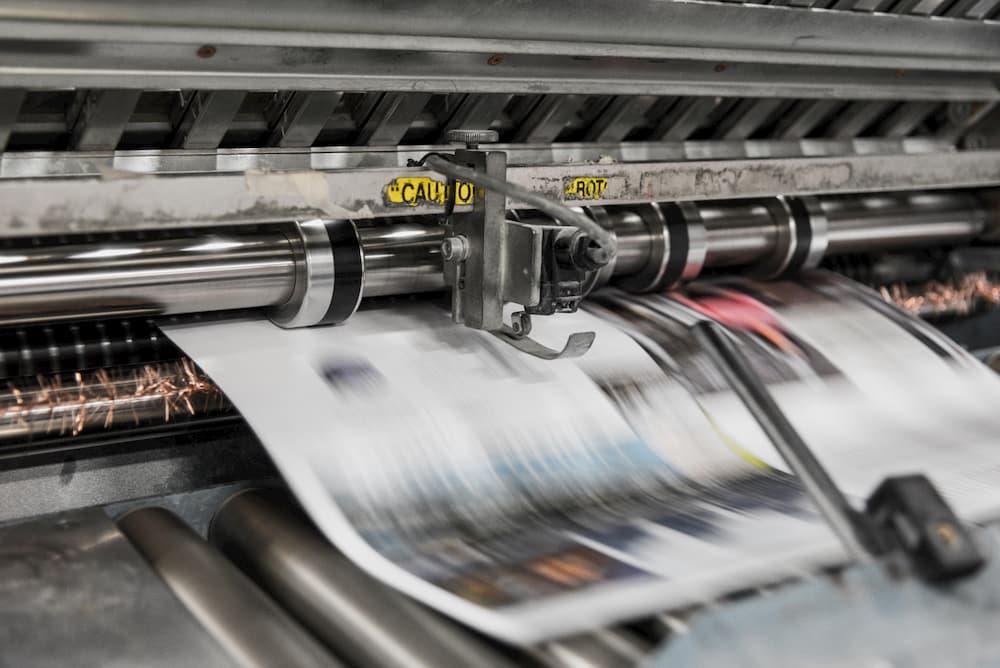 Imagen de un ejemplar de periódico saliendo de la imprenta.