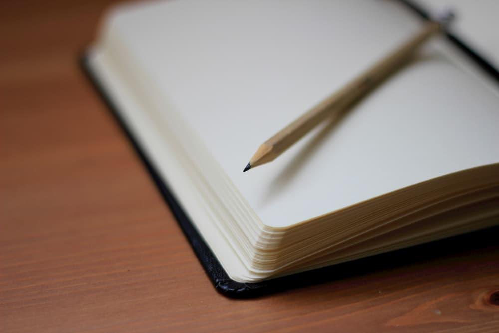 Imagen de una libreta con las hojas en blanco con un lápiz apoyado por encima