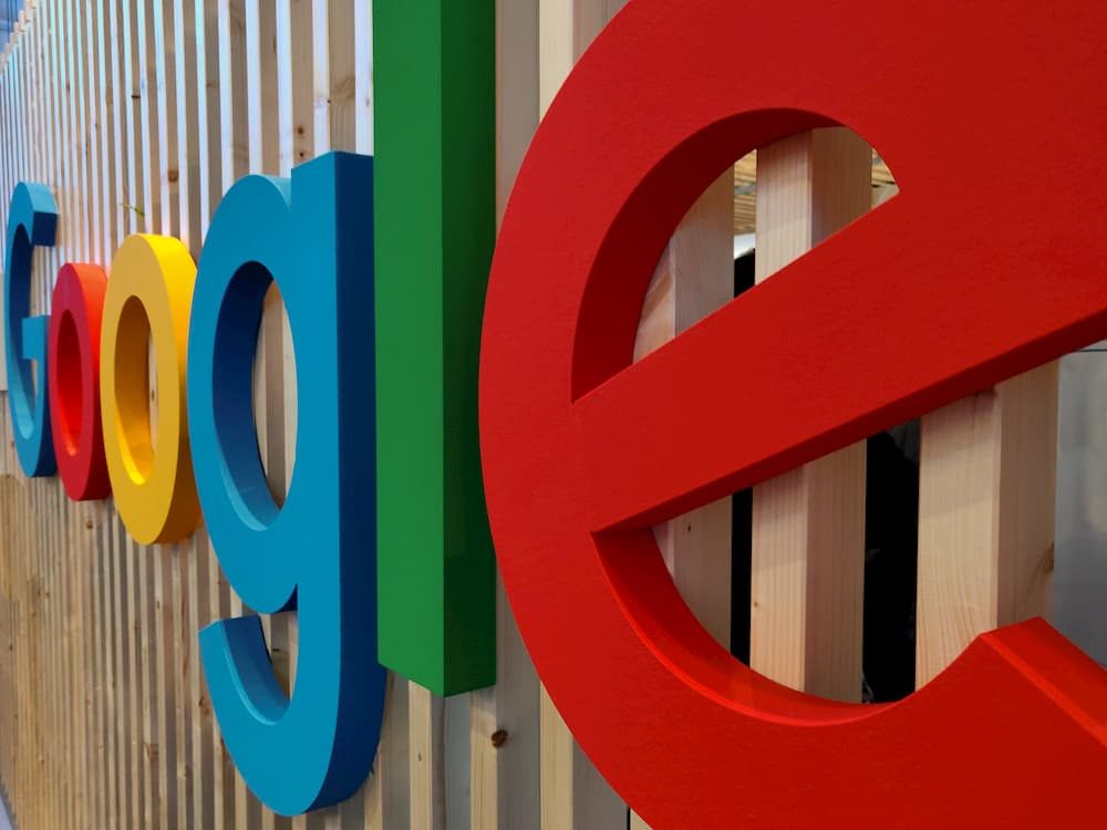 Imagen del logo de Google escrito en letras gigantes apoyadas en una pared.