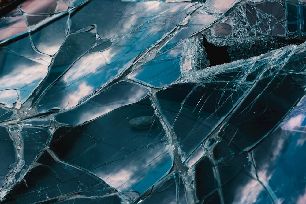 Imagen de la luna de un coche con el cristal roto en varios trozos.
