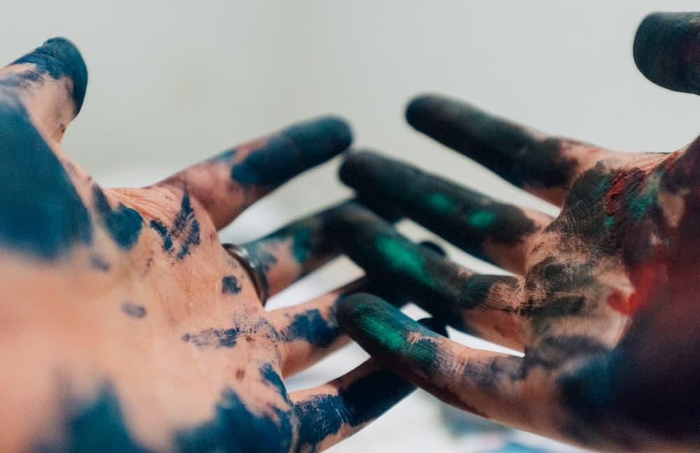 Imagen de las manos boca arriba manchadas en pintura de una persona