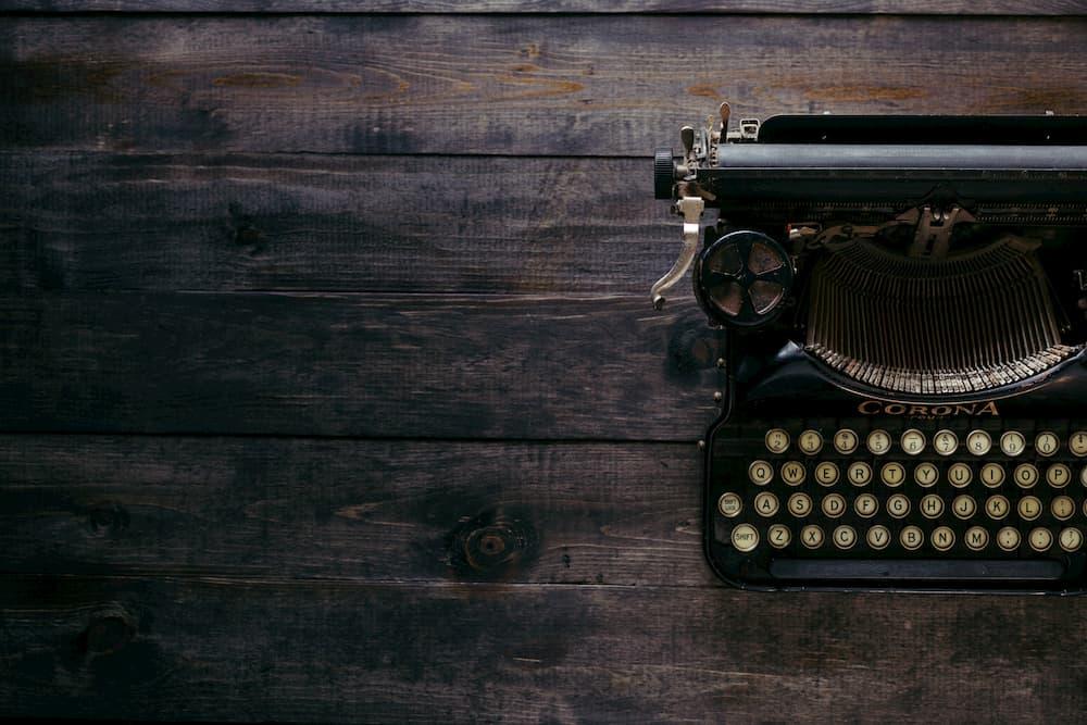Imagen de una máquina de escribir encima de una mesa, como precursora de lo que es en la actualidad escribir en sistemas informáticos.