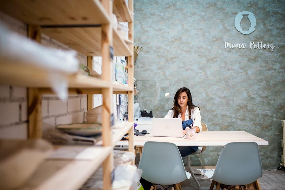 Imagen de Marina García sentada en su mesa de trabajo en Mama Pottery