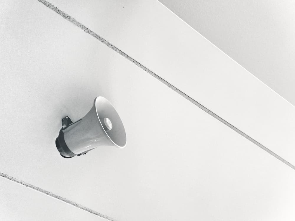 Imagen en blanco y negro de un megáfono colgado del techo