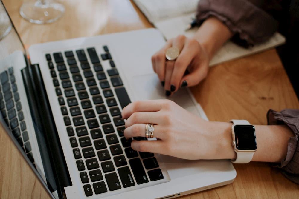 Imagen de una mujer escribiendo en un Macbook Pro