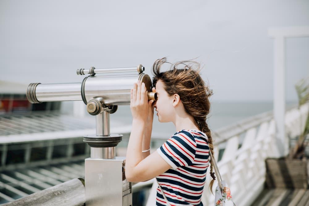 Imagen de una mujer observando el horizonte a través de un telescopio
