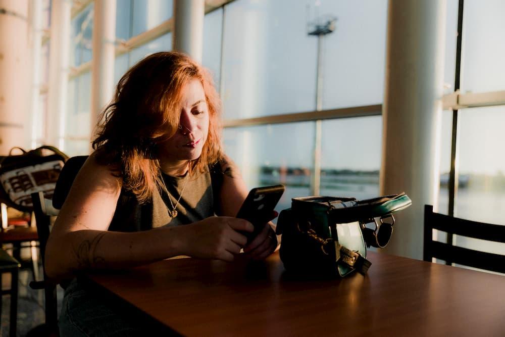 Imagen de una mujer revisando su smartphone mientras espera en un aeropuerto.