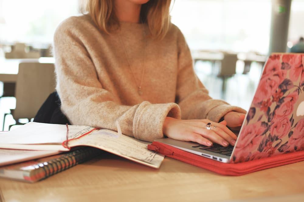 Imagen de una mujer trabajando con su portátil con libretas a su lado
