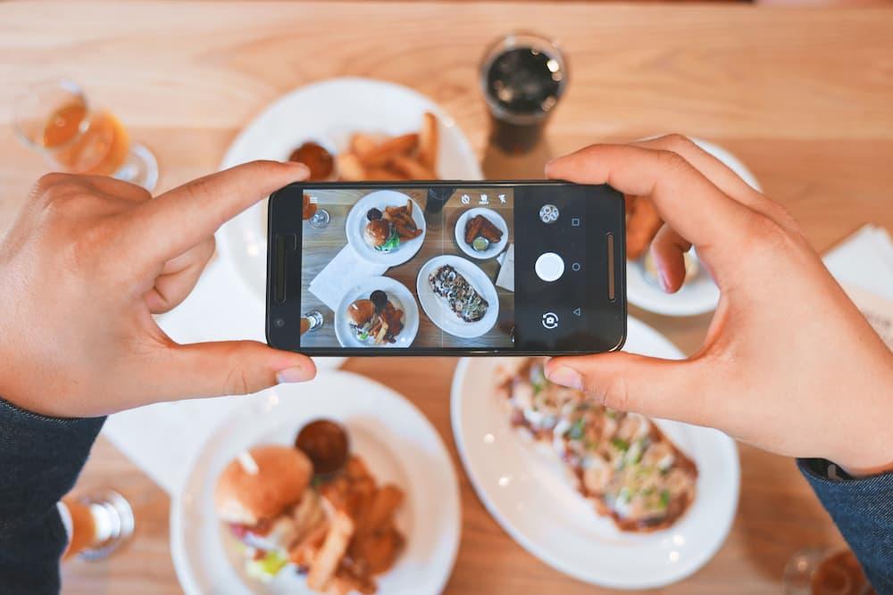 Imagen de una mujer fotografiando comida con su teléfono
