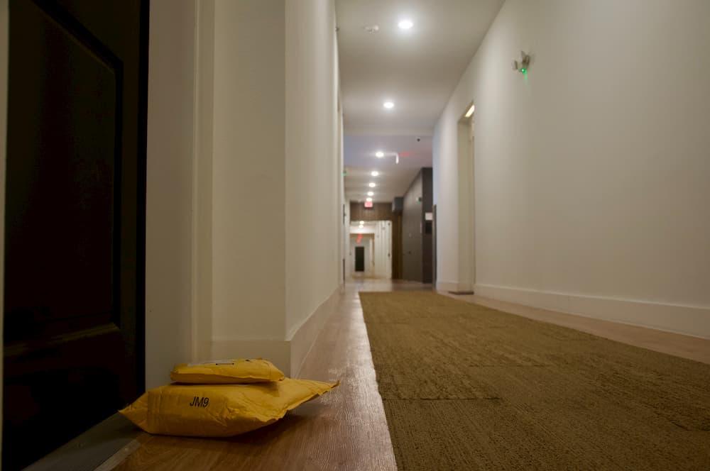 Imagen de un paquete entregado en la puerta de la habitación de un hotel.