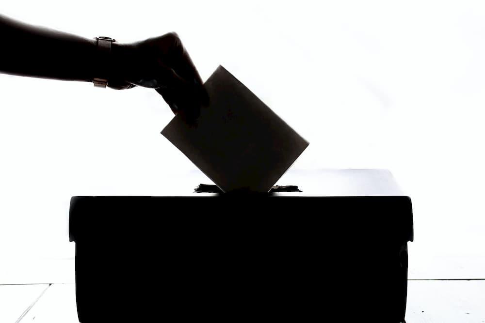 Imagen de una persona insertando un sobre en una urna de elecciones.