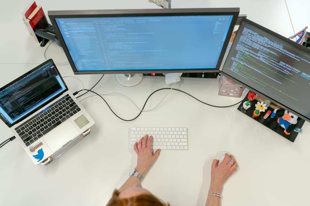 Imagen de una perspna usando tres pantallas de ordenador a la vez.