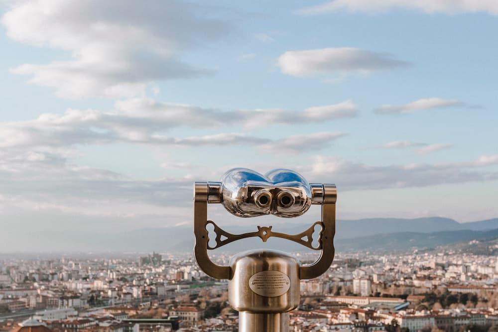 Imagen de unos prismáticos situados en lo alto de una ciudad para verla.