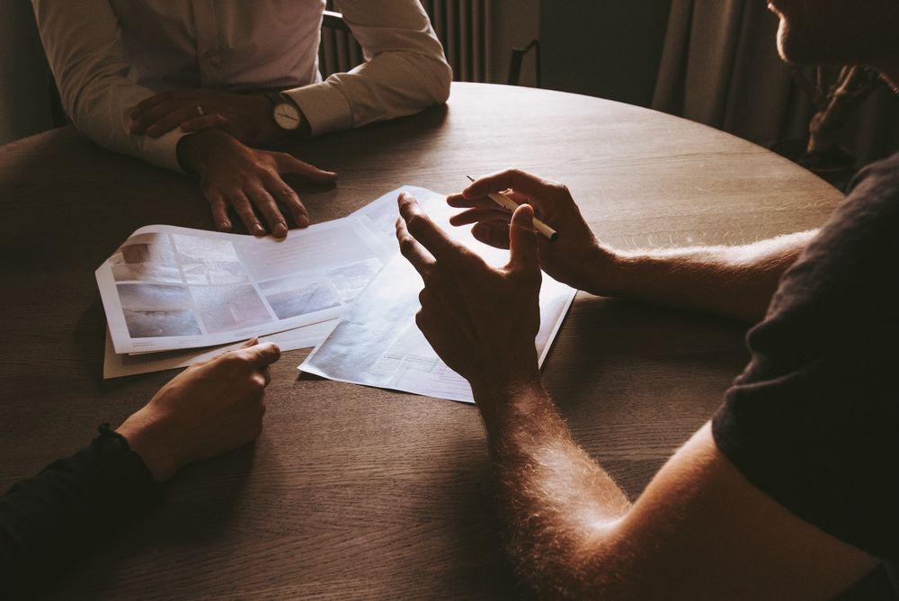 Imagen de varias personas sentadas en torno a una mesa negociando un contrato de diseño web