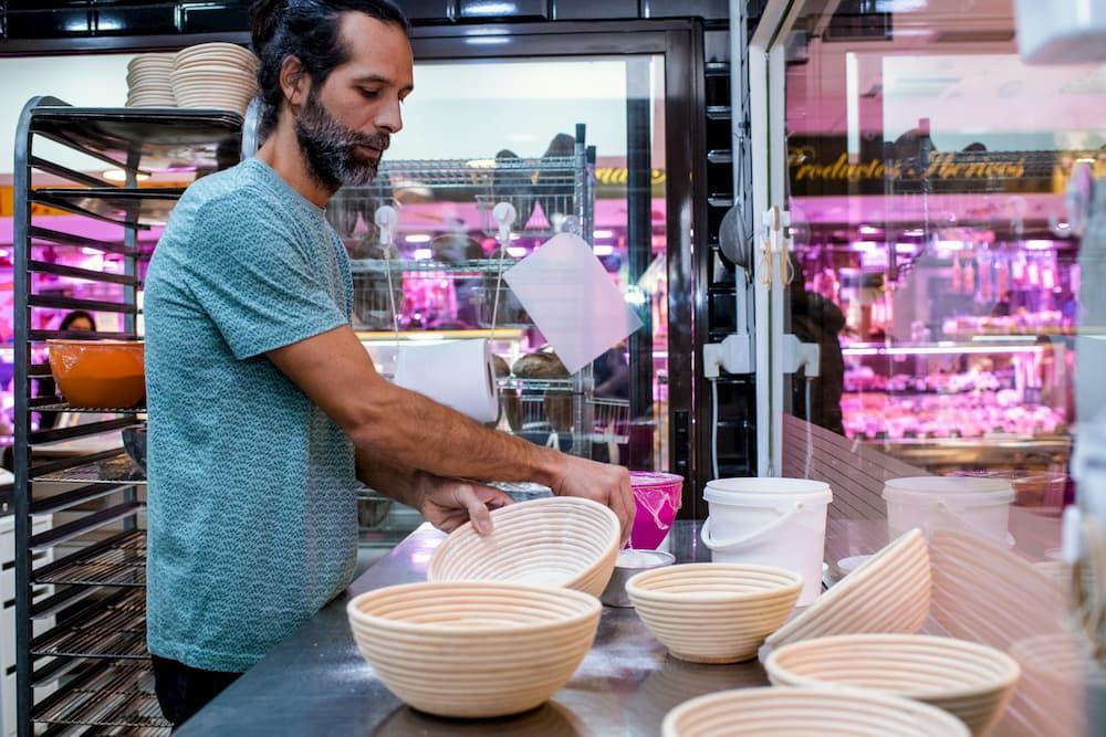 Imagen de Sergio, de Celikatessen, empleando cestas para elaborar pan en su obrador.
