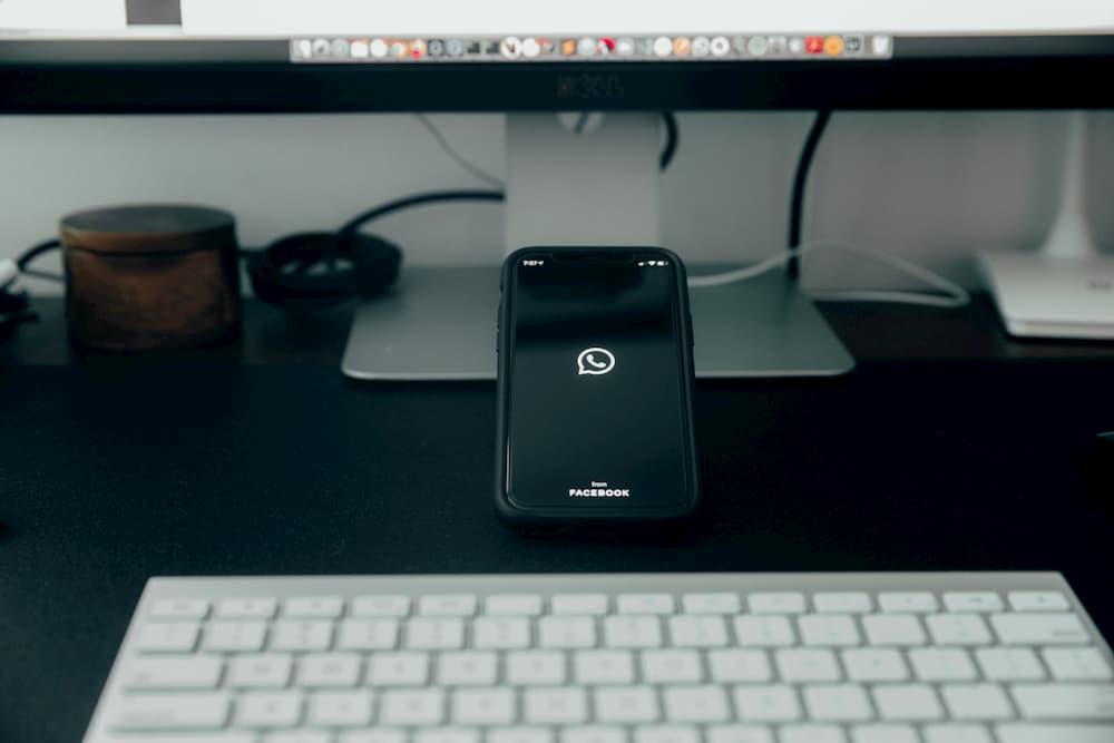 Imagen de un smartphone abriendo la app de WhatsApp con fondo negro.