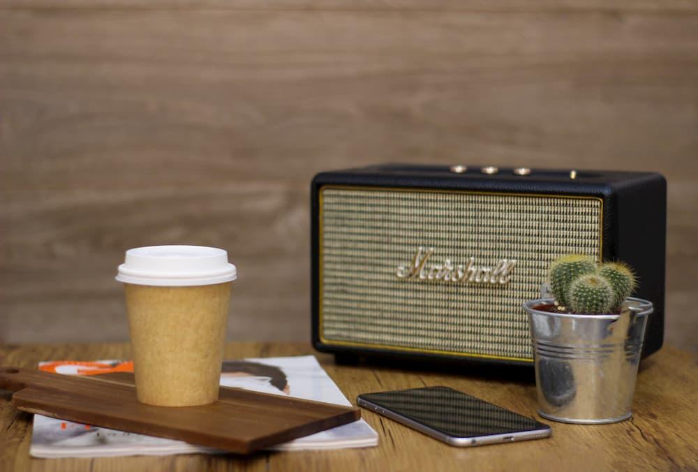 Imagen de un smartphone al lado de un altavoz Marshall con Bluetooth.