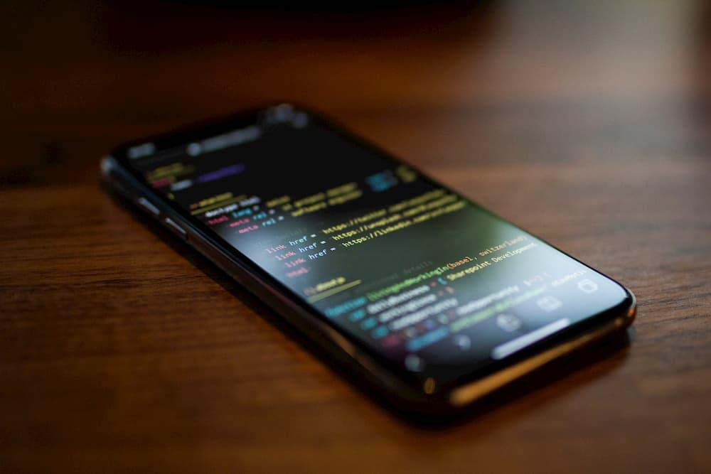 Imagen de un smartphone mostrando en pantalla código de programación HTML