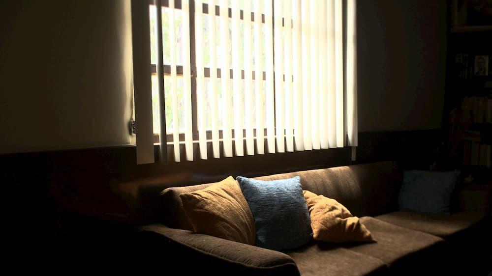 Imagen de un sofá iluminado por una ventana situada detrás.