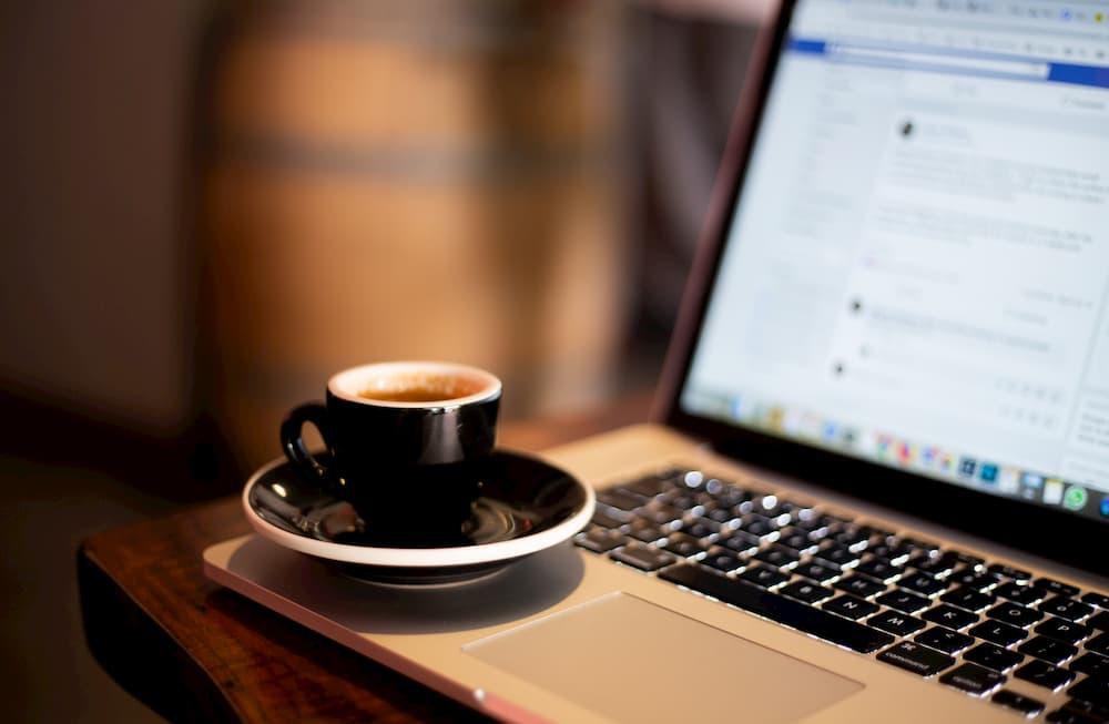 Imagen de una taza de café al lado de un portátil con Facebook abierto