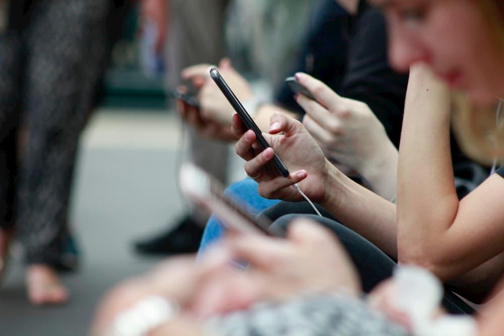 Imagen de varias personas usando sus teléfonos móviles en el metro